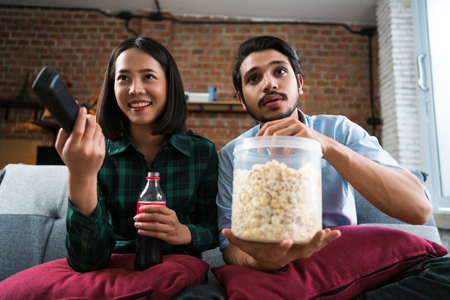Couple watching movie at home happily. They sit on sofa, eat soft drinks and popcorn while watching movies.