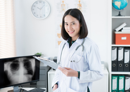 The doctor is sitting in the room to see the patient. She is opening x-ray effects.