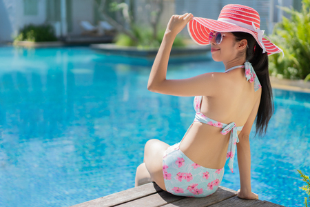 Woman is sitting she wears a bikini relaxing in the summer, she is in the pool. Stock Photo