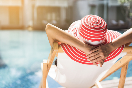 Woman is sitting in a chair relaxing in the summer, she is in the pool.