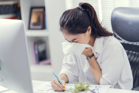 Las mujeres estornudan y tienen frío. Ella está en la oficina.