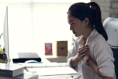 Die Geschäftsfrau tut ihrem Herzen weh und ist im Büro.