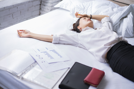 Business woman She felt stressed After work She relaxed in bed. Stock Photo
