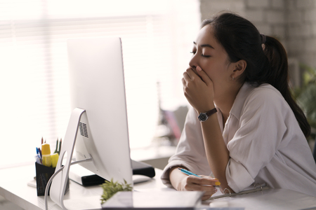 Businesswoman, yawned she was tired of working in an office. 스톡 콘텐츠