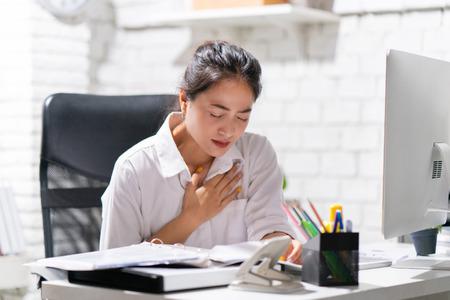 Business woman heart disease she is working in an office.