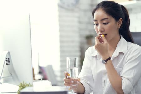 Geschäftsfrau, die Wasser trinkt und Medizin nimmt. Sie fühlt sich krank Standard-Bild