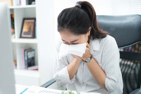 Women are sneezing and are cold. She is in the office.