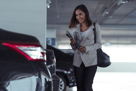 donna d'affari asiatica sta aprendo l'auto con una chiave remota, sta andando a casa. Archivio Fotografico