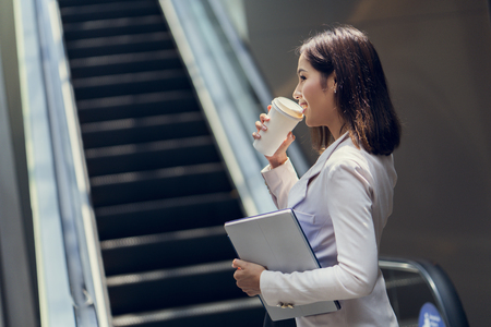 Business woman She is going to work in her morning at the subway. And she is eating coffee