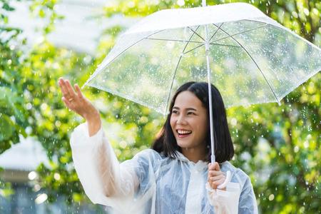 Asiatische Frau des regnerischen Tages, die draußen einen Regenmantel trägt. Sie ist glücklich. Sie benutzte ihre Hand, um den Regen zu berühren.