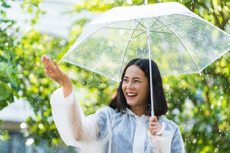 Rainy day asian woman wearing a raincoat outdoors. She is happy.She used her hand to touch the rain. Banque d'images