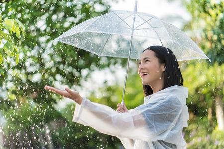 Mujer asiática de día lluvioso con un impermeable al aire libre. Ella es feliz Usó su mano para tocar la lluvia. Foto de archivo