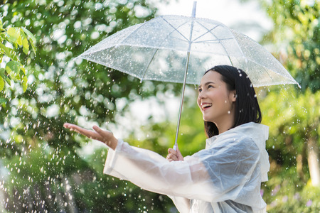 Rainy day asian woman wearing a raincoat outdoors. She is happy.She used her hand to touch the rain. Banco de Imagens
