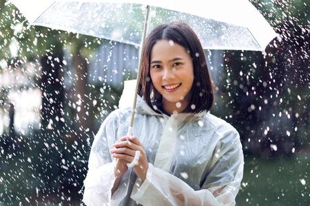 Mujer asiática de día lluvioso con un impermeable al aire libre. Ella es feliz.