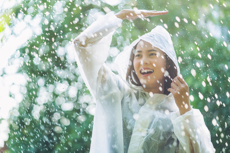 Rainy day asian woman wearing a raincoat outdoors. She is happy. Imagens