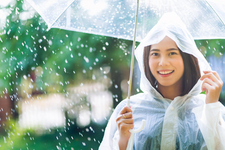 Rainy day asian woman wearing a raincoat outdoors. She is happy. 스톡 콘텐츠