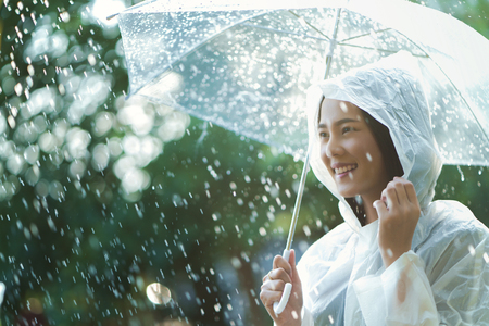 Rainy day asian woman wearing a raincoat outdoors. She is happy. Stock fotó - 114060330