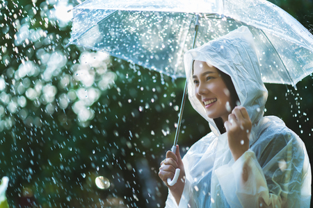 Rainy day asian woman wearing a raincoat outdoors. She is happy. Banque d'images