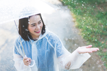 Rainy day asian woman wearing a raincoat outdoors. She is happy.She used her hand to touch the rain. Stock Photo