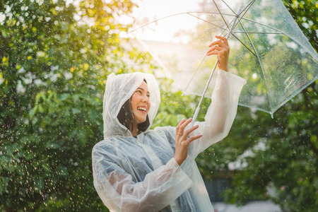 Rainy day asian woman wearing a raincoat outdoors. She is happy. Stock Photo