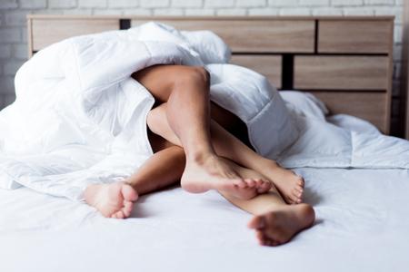 Close-up van gepassioneerd jong Aziatisch stel dat op bed ligt. Ze zijn seks beu.