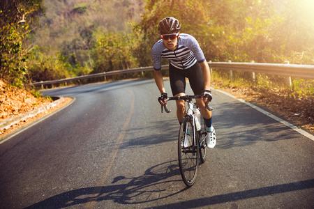 Asiatischer Mann, der morgens Rennrad radelt. Er ist auf einer Forststraße. Standard-Bild