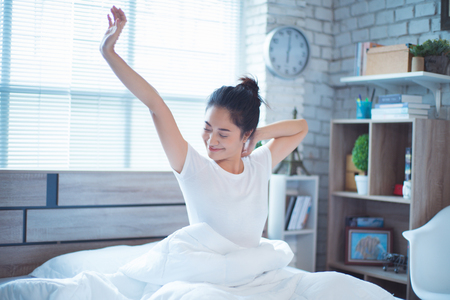 Asiatische Frau, die morgens im Bett trainiert, fühlt sich erfrischt.