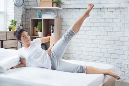 Asian woman exercising in bed in the morning, she feels refreshed.