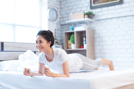 Asian woman exercising in bed in the morning, she feels refreshed. Banco de Imagens - 120465582