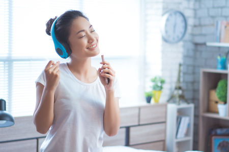 Asian woman  listening to music and  sings in the room happily Stock Photo