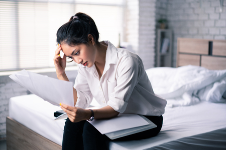 Business woman felt stressed after work and sitting on bed. Stock Photo