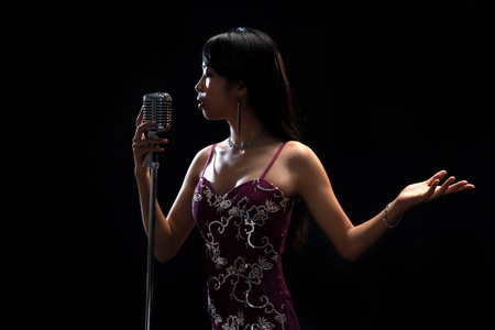 Asian woman singer holding a microphone singing.