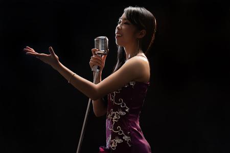 Cantante de mujer asiática sosteniendo un micrófono cantando. Foto de archivo