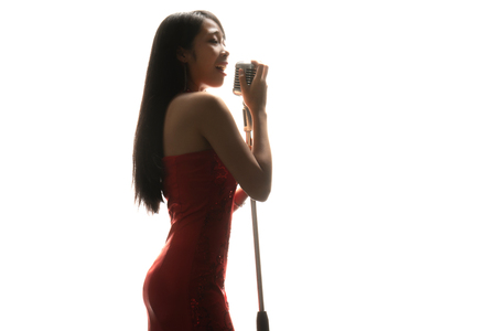 Asian woman singer holding a microphone singing. 版權商用圖片 - 120465912
