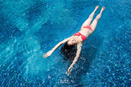 Aziatische vrouw die bij het zwembad zwemt
