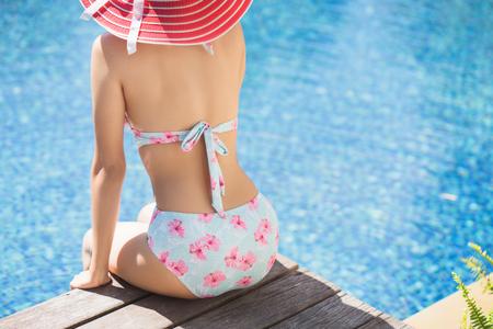 Woman in  bikini relaxing by the pool. Stock Photo