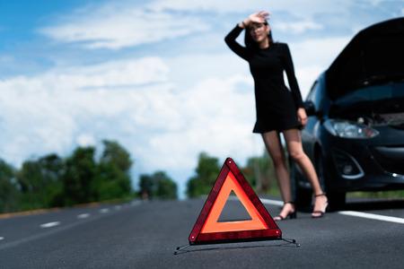 La voiture d'une femme asiatique est cassée. Elle attend que quelqu'un l'aide.