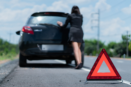 Asian womans car  broken.She is waiting for someone to help.
