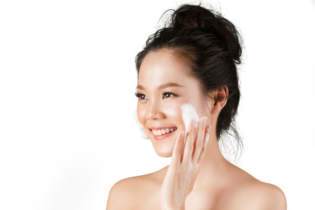 Asian woman use  facial foam to wash cosmetics off the face.