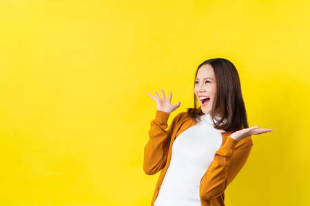 Asian girl is surprised. She is excited.Yellow background studio 免版税图像 - 123512130