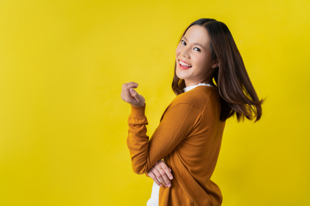 happy asian woman in yellow background 스톡 콘텐츠