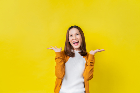 La ragazza asiatica è sorpresa. Lei è eccitata. Studio di sfondo giallo Archivio Fotografico