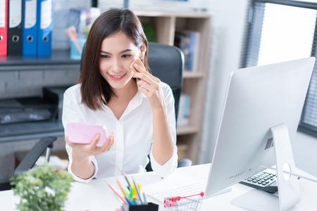 Frau, die während der Arbeit in ihrem Büro schminkt. Standard-Bild