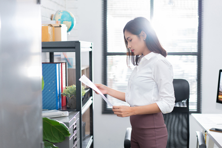 Asian woman viewing documents in the office.
