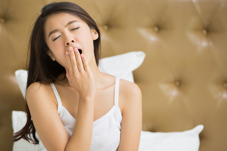 Asian woman  yawning after she wake up. Stock Photo