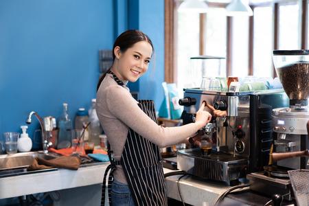 Barista mujer asiática haciendo café en una tienda