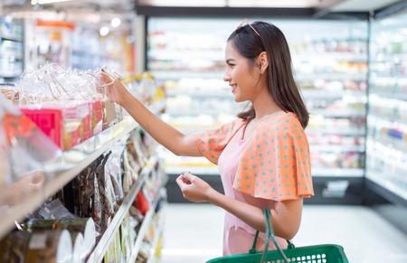 De vrouw is in de supermarkt om eten te kopen