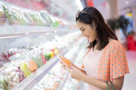 La mujer está en el supermercado comprando comida.