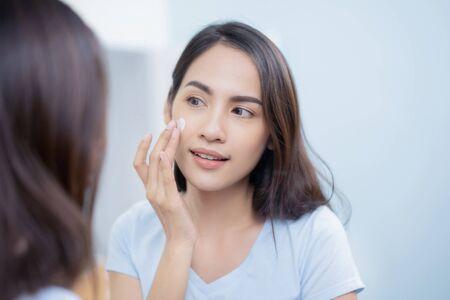Asian women applying face lotion. 스톡 콘텐츠