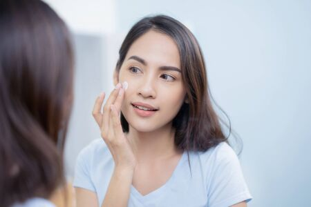 Asian women applying face lotion. Imagens